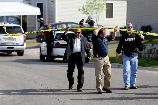 Investigators come out of the area in Summit Ridge where a suspect was encountered after a police shooting in Converse Friday afternoon. Photo: TOM REEL