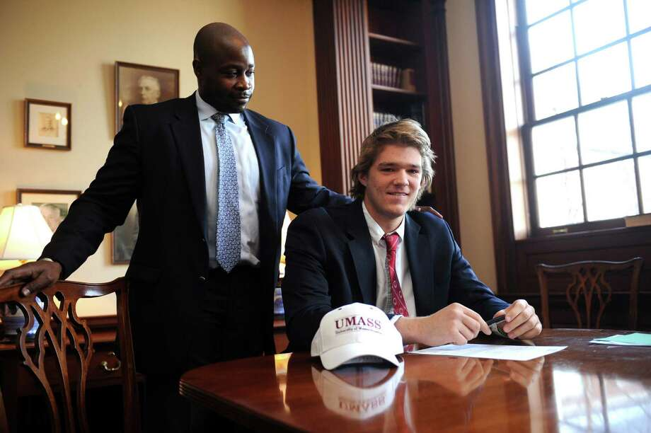 Coach Jarrett Shine watches while Brunswick School quarterback Todd Stafford signs National Letter of Intent to play football at University of Massachusetts, Wednesday, Feb.6, 2013. at Brunswick in Greenwich, Conn. Photo: Helen Neafsey / Greenwich Time