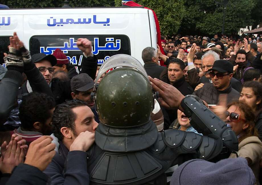 A police officer in riot gear salutes the ambulance carrying the body of slain opposition leader Chokri Belaid in Tunis. Photo: Amine Landoulsi, Associated Press