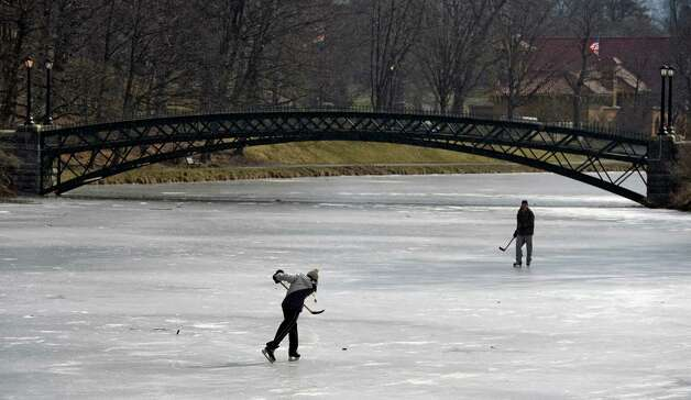 SUNYA students Cory Stadd, foreground, and Dave Rinaldo have a friendly game of ice hockey Wednesday morning Feb 6, 2013 on Washington Park Lake in Albany, N.Y.  (Skip Dickstein/Times Union) Photo: SKIP DICKSTEIN