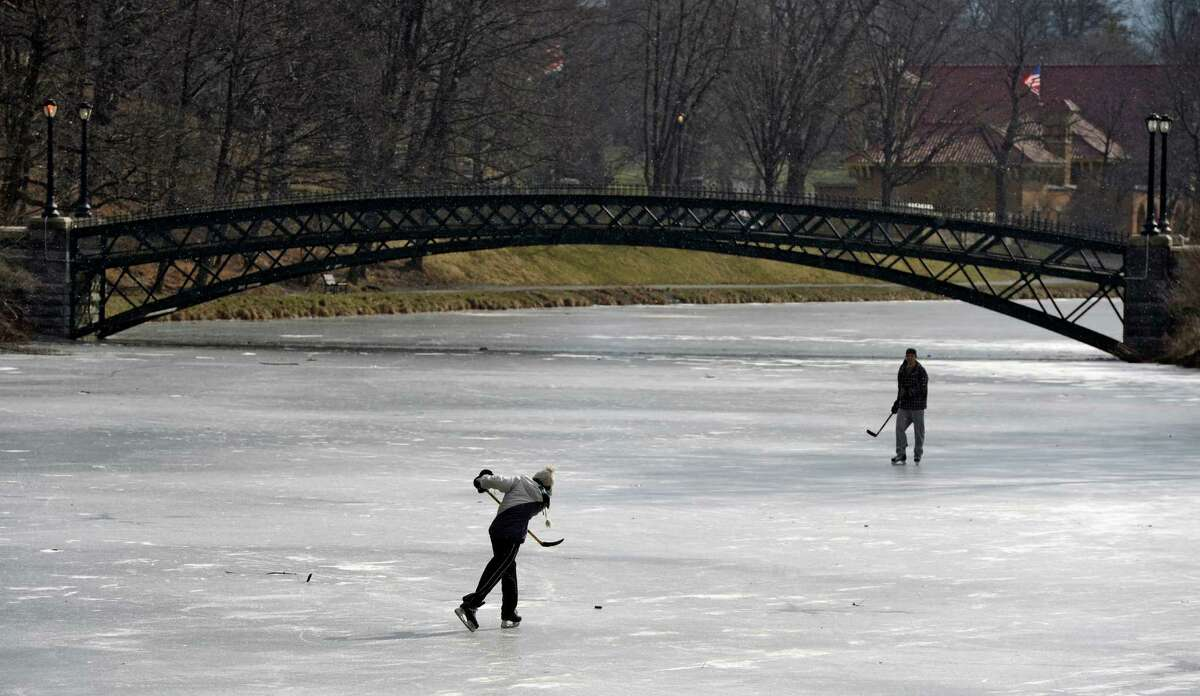 SUNYA students Cory Stadd, foreground, and Dave Rinaldo have a friendly game of ice hockey Wednesday morning Feb 6, 2013 on Washington Park Lake in Albany, N.Y. (Skip Dickstein/Times Union)