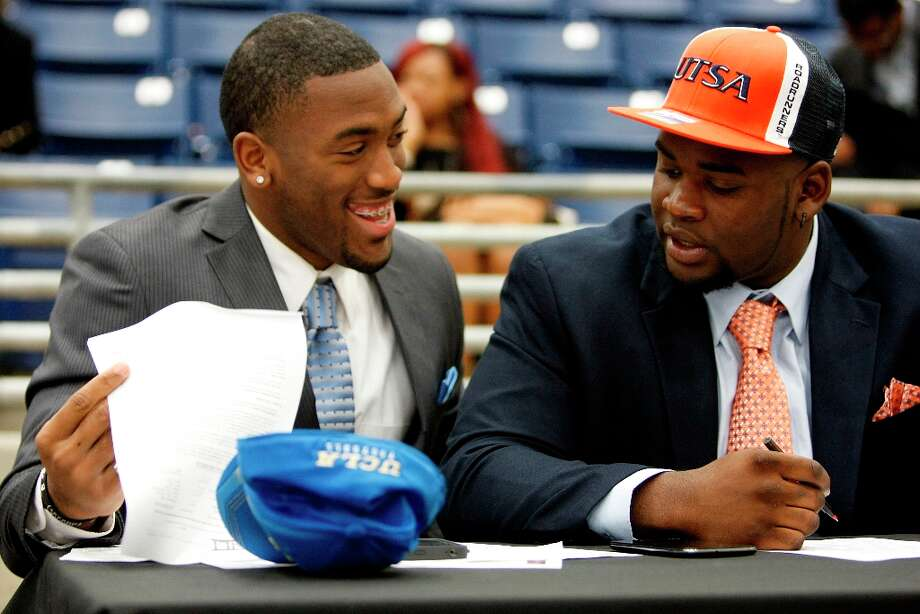Fort Bend Marshall linebacker Deon Hollins Jr., left, who committed to play football at UCLA, shares a laugh with teammate Anthony Lee who committed to the University of Texas San Antonio during a signing day ceremony at the Buddy Hopson Field House on Tuesday in Missouri City. Photo: Johnny Hanson / © 2013  Houston Chronicle