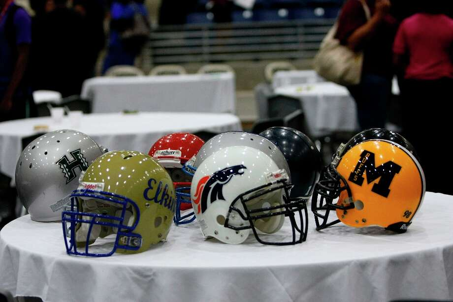 Fort Bend ISD High School football helmets sit on a table. Photo: Johnny Hanson / © 2013  Houston Chronicle