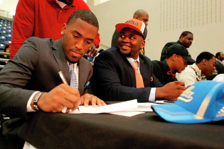 Fort Bend Marshall linebacker Deon Hollins Jr., left, signs during a mock commitment letter to play football at UCLA, next to  teammate Anthony Lee who committed to the University of Texas San Antonio. Photo: Johnny Hanson / © 2013  Houston Chronicle