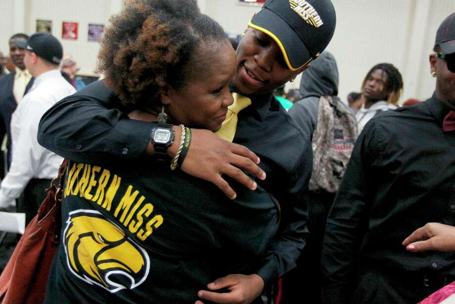 Hightower High School's Kelsey Douglas gets a hug from his mother Ingrid Douglas as he made his commitment to play football at Southern Miss. Photo: Johnny Hanson / © 2013  Houston Chronicle