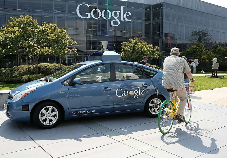 A bicyclist passes a self-driving car at Google headquarters in Mountain View. The cars can be tested on the road in California. Photo: Justin Sullivan, Getty Images