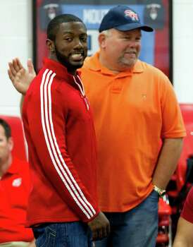 Adam Taylor, left, gets a pat on the back from Doug Sowell during a National Letter of Intent signing ceremony at Katy High School Wednesday, Feb. 6, 2013, in Katy. Taylor signed a letter of intent to play football at Nebraska. Photo: Brett Coomer, Houston Chronicle / © 2013 Houston Chronicle