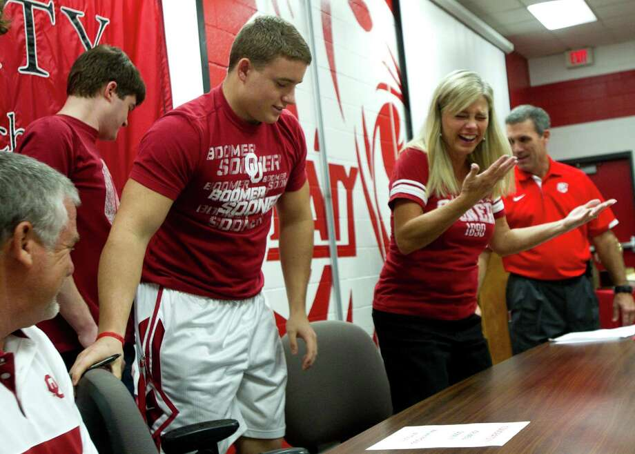 Oklahoma signee Matt Dimon, pulls out a chair for his mother, Cindi Dimon, during a National Letter of Intent signing ceremony at Katy High School Wednesday, Feb. 6, 2013, in Katy. Photo: Brett Coomer, Houston Chronicle / © 2013 Houston Chronicle