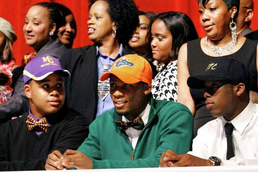 Wide receiver Marqui Hawkins, center, sits with Carver High School teammates John Thomas, left, and Dany Ryles, right, during Signing Day events at the school auditorium in Columbus, Ga., Wednesday, Feb 6, 2013. Hawkins signed his letter of intent with Florida, Thomas with Miles College and Ryles with West Georgia Technical College. (AP Photo/The Ledger-Enquirer, Robin Trimarchi) Photo: Robin Trimarchi, Associated Press / The Ledger-Enquirer