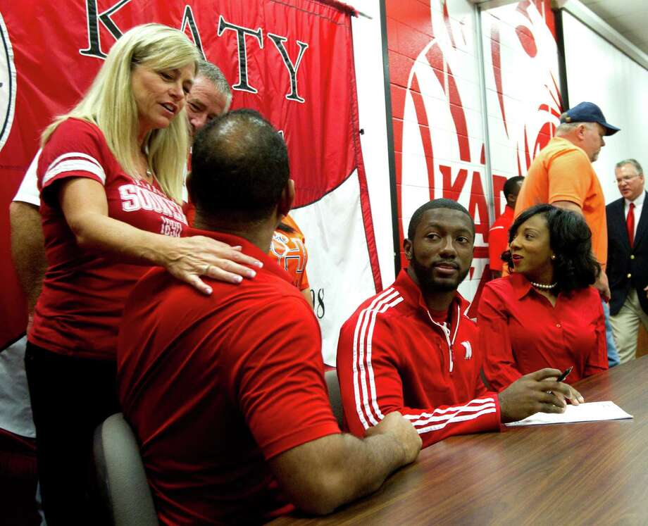 Cindi Dimon, left, congratulates Barry Taylor, father of Nebraska signee Adam Taylor, right, during a National Letter of Intent signing ceremony at Katy High School Wednesday, Feb. 6, 2013, in Katy. Dimon's son, Matt, signed to play football at Oklahoma. Photo: Brett Coomer, Houston Chronicle / © 2013 Houston Chronicle
