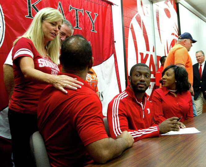 Cindi Dimon, left, congratulates Barry Taylor, father of Nebraska signee Adam Taylor, right, during