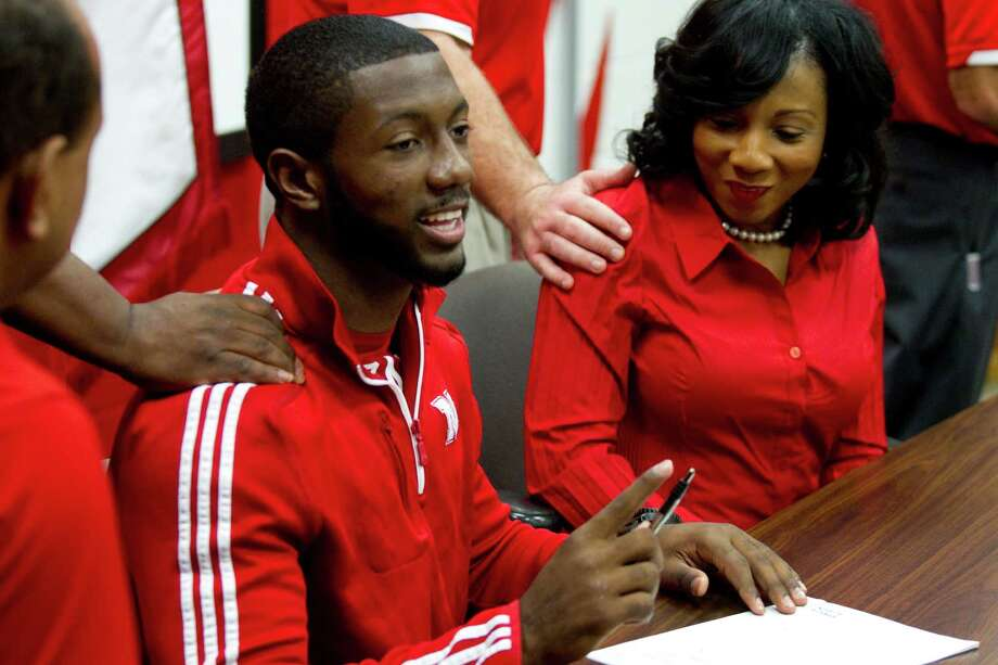 Nebraska signee Adam Taylor, left, and his mother, Fedora Taylor, right, get pats on the back during a National Letter of Intent signing ceremony at Katy High School Wednesday, Feb. 6, 2013, in Katy. Photo: Brett Coomer, Houston Chronicle / © 2013 Houston Chronicle