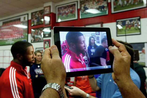 Nebraska signee Adam Taylor is photographed on an iPad by his father, Barry, during a National Letter of Intent signing ceremony at Katy High School Wednesday, Feb. 6, 2013, in Katy. Photo: Brett Coomer, Houston Chronicle / © 2013 Houston Chronicle