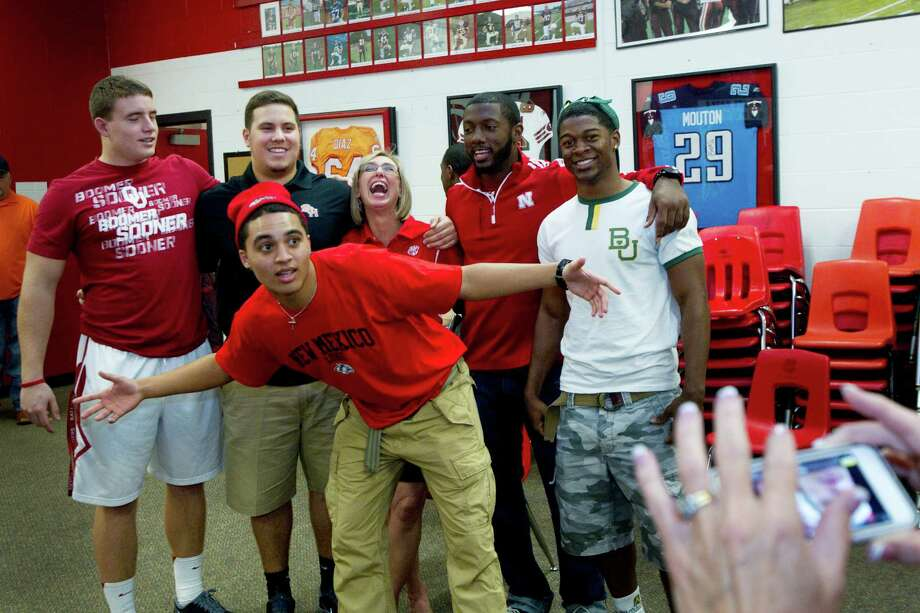 New Mexico signee Isaiah Brown, center, jumps in front of a photo of his teammates during a National Letter of Intent signing ceremony at Katy High School Wednesday, Feb. 6, 2013, in Katy. Photo: Brett Coomer, Houston Chronicle / © 2013 Houston Chronicle