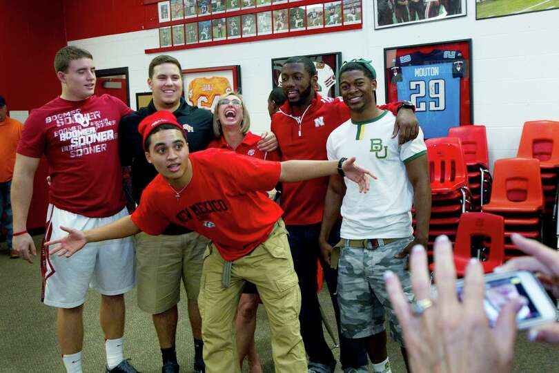 New Mexico signee Isaiah Brown, center, jumps in front of a photo of his teammates during a National