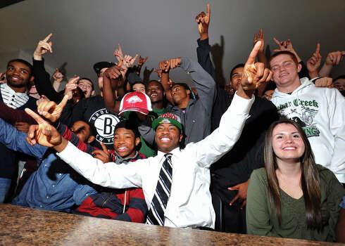 Cedar Creek High School's Damon Mitchell, center, celebrates with teammates after signing a letter of intent to play NCAA college football for Arkansas State, Wednesday, Feb. 6, 2013, in Egg Harbor City, N.J. (AP Photo/The Press of Atlantic City, Michael Ein) MANDATORY CREDIT Photo: Michael Ein, Associated Press / The Press of Atlantic City