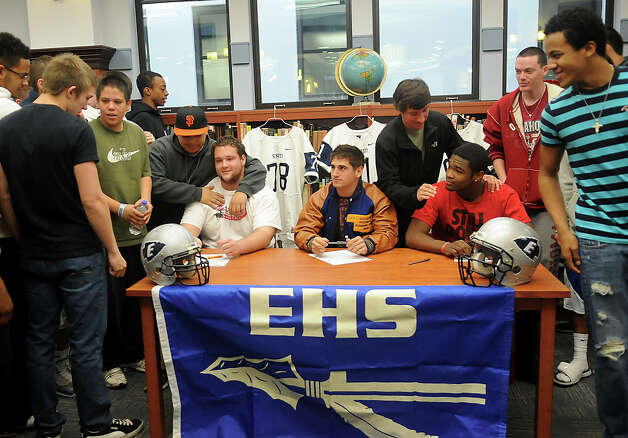 Enid High School Plainsmen, seated from elft, Logan Miller, Seth Handley and Lance Smith, receive congratulations from their teammates during national signing day at the EHS Library, Wednesday, Feb. 6, 2013, in Enid, Okla. (AP Photo/Enid News and Eagle, Bonnie Vculek) Photo: BONNIE VCULEK, Associated Press / Enid News And Eagle