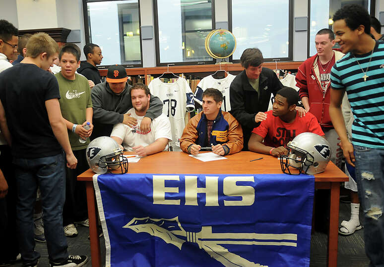 Enid High School Plainsmen, seated from elft, Logan Miller, Seth Handley and Lance Smith, receive co