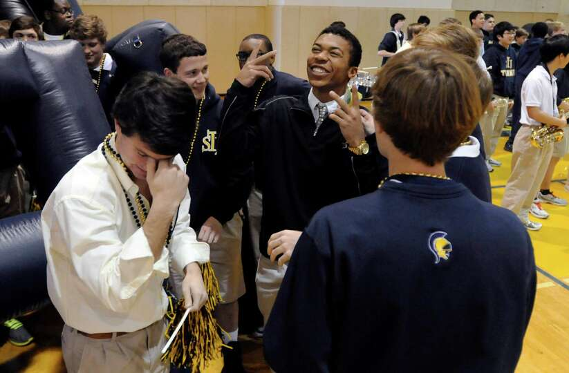 Saint James' CJ Duncan (center) talks to teammates before signing a letter of intent to attend and p