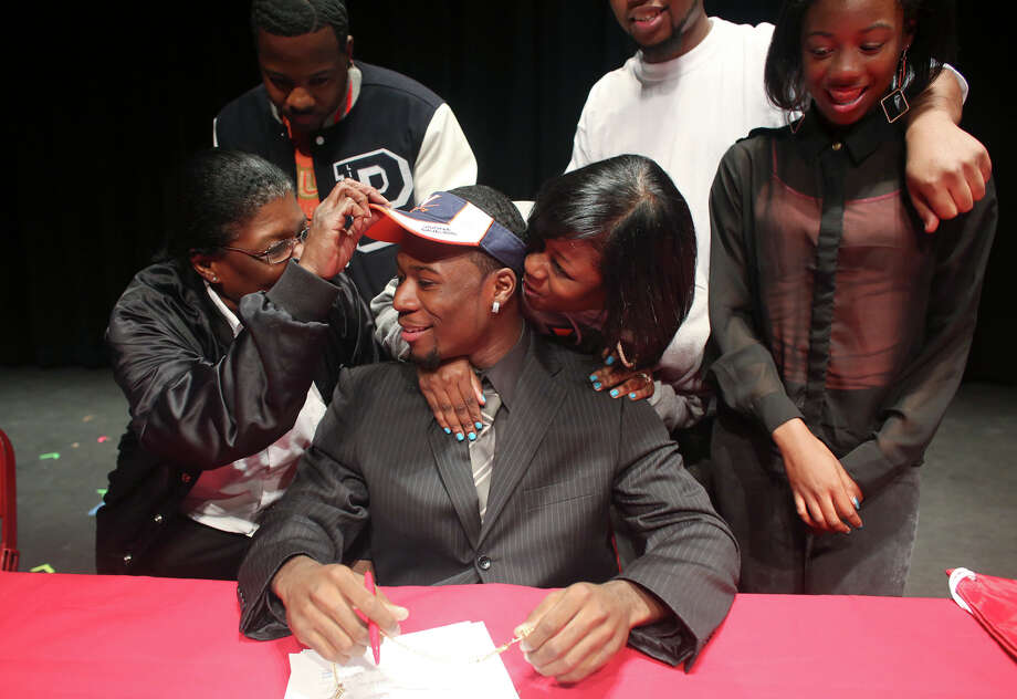 Bayside High School running back Taquan Mizzell sits in front of family members Wednesday, Feb. 6, 2013, at the high school in Virginia Beach, Va., where he signed a letter of intent with Virginia. From left are Dorothy Hambric, Courtney Littlejohn, Dyshell Gardner, Jerome Williams and Dekeara Mizzell. (AP Photo/The Virginian-Pilot, Ross Taylor) MAGS OUT Photo: Ross Taylor, Associated Press / The Virginian-Pilot