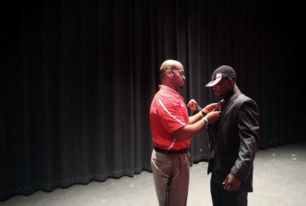 Bayside High School running back Taquan Mizzell gets a little help from coach Jonathan White in adjusting his tie, before signing a letter of intent with Virginia on Wednesday, Feb. 6, 2013, in Virginia Beach, Va. (AP Photo/The Virginian-Pilot, Ross Taylor) MAGS OUT Photo: Ross Taylor, Associated Press / The Virginian-Pilot