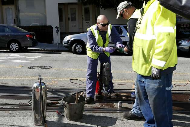 San Francisco Municipal Transit Authority personnel repair a portion of a track where an incident involving a cable car resulted in seven injuries near the intersection of Powell and Washington Streets on Wednesday, February 6, 2013 in San Francisco, Calif. Photo: Beck Diefenbach, Special To The Chronicle
