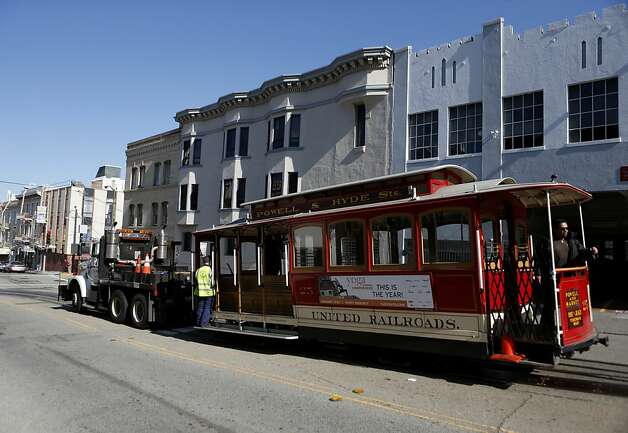 A cable car is towed away as San Francisco Municipal Transit Authority personnel inspect a portion of a track where an incident involving a cable car resulted in seven injuries near the intersection of Powell and Washington Streets on Wednesday, February 6, 2013 in San Francisco, Calif. Photo: Beck Diefenbach, Special To The Chronicle