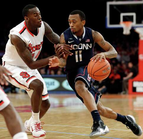 St. John's forward Jakarr Sampson (14) defends as Connecticut guard Ryan Boatright (11) drives toward the basket in the first half of their NCAA college basketball game at Madison Square Garden in New York, Wednesday, Feb. 6, 2013. (AP Photo/Kathy Willens) Photo: Kathy Willens, Associated Press / AP