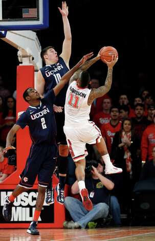 Connecticut forwards DeAndre Daniels (2) and Tyler Olander (10) defend as St. John's guard D'Angelo Harrison (11) shoots a layup in the first half of their NCAA college basketball game at Madison Square Garden in New York, Wednesday, Feb. 6, 2013. (AP Photo/Kathy Willens) Photo: Kathy Willens, Associated Press / AP