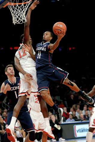 St. John's Chris Obekpa (12) defends as Connecticut guard Ryan Boatright (11) shoots a layup during the first half of their NCAA college basketball game, Wednesday, Feb. 6, 2013, at Madison Square Garden in New York. (AP Photo/Kathy Willens) Photo: Kathy Willens, Associated Press / AP