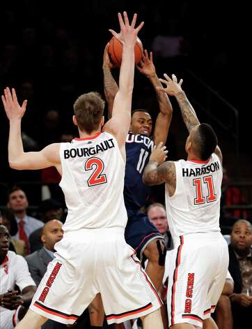 Connecticut guard Ryan Boatright (11) tries to pass against St. John's Marco Bourgault (2) and Phil Greene IV (11) during the first half of their NCAA college basketball game, Wednesday, Feb. 6, 2013, at Madison Square Garden in New York. (AP Photo/Kathy Willens) Photo: Kathy Willens, Associated Press / AP