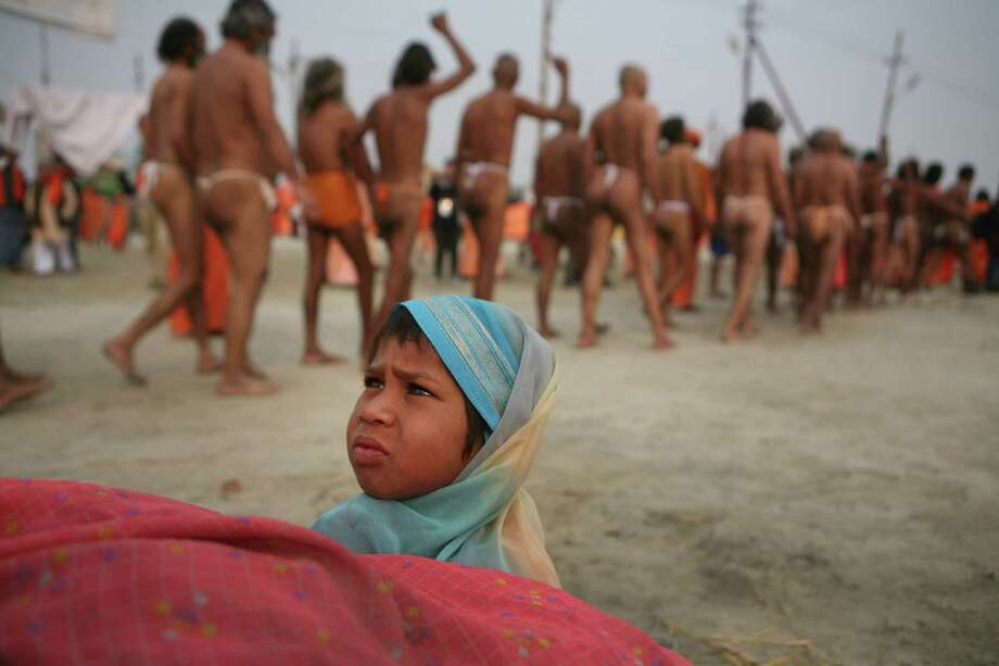 A child watches as  Hindu holy men of the Juna Akhara sect leave their camp for a rituals that are believed to rid them of all ties in this life and dedicate themselves to serving God as a 'Naga' or naked holy men, at Sangam, the confluence of the Ganges and Yamuna River during the Maha Kumbh festival in Allahabad, India, Wednesday, Feb. 6, 2013. The significance of nakedness is that they will not have any worldly ties to material belongings, even something as simple as clothes. This ritual that transforms selected holy men to Naga can only be done at the Kumbh festival. Photo: Rajesh Kumar Singh, Associated Press / AP