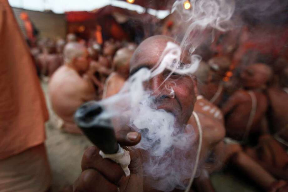 "Hindu holy men of the Juna Akhara sect smokes tobacco in between a rituals that are believed to rid them of all ties in this life and dedicate themselves to serving God as a ""Naga"" or naked holy men, at Sangam, the confluence of the Ganges and Yamuna River during the Maha Kumbh festival in Allahabad, India, Wednesday, Feb. 6, 2013. The significance of nakedness is that they will not have any worldly ties to material belongings, even something as simple as clothes. This ritual that transforms selected holy men to Naga can only be done at the Kumbh festival. Photo: Rajesh Kumar Singh, Associated Press / AP"