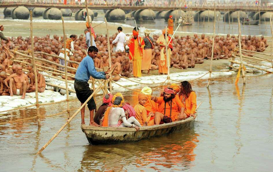 Newly initiated 'naga sadhus' prepare to perform rituals on the banks of the Ganga River during the