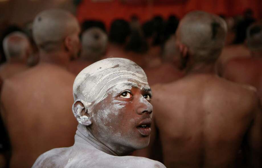 """A Naga Sadhu, center, watches as other Hindu holy men of the Juna Akhara sect participate in a rituals that are believed to rid them of all ties in this life and dedicate themselves to serving God as a """"Naga"""" or naked holy men, at Sangam, the confluence of the Ganges and Yamuna River during the Maha Kumbh festival in Allahabad, India, Wednesday, Feb. 6, 2013. The significance of nakedness is that they will not have any worldly ties to material belongings, even something as simple as clothes. This ritual that transforms selected holy men to Naga can only be done at the Kumbh festival. Photo: Rajesh Kumar Singh, Associated Press / AP"""