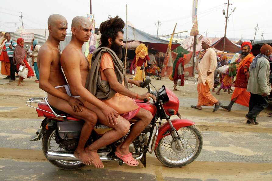 Two Hindu holy men of the Juna Akhara sect  are being take on a motorcycle by their teacher as they