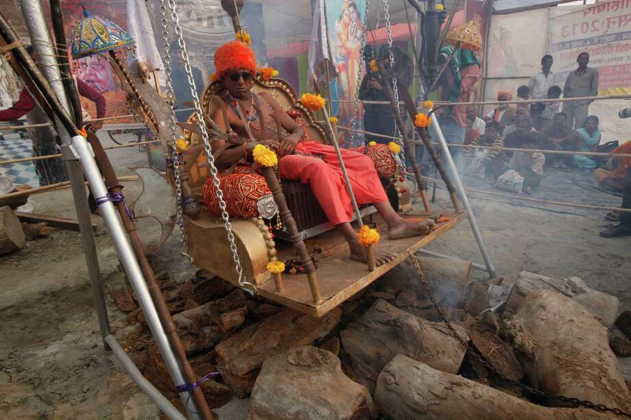 "A Hindu holy man sits on a chair of nails placed on a metallic swing hung above fire at ""Sangam,"" the confluence of rivers Ganges and Yamuna during the Maha Kumbh festival in Allahabad, Monday, Feb. 4, 2013. Millions of Hindu pilgrims are expected to attend the Maha Kumbh festival, which is one of the world's largest religious gatherings that lasts 55 days and falls every 12 years. Photo: Rajesh Kumar Singh, Associated Press / AP"