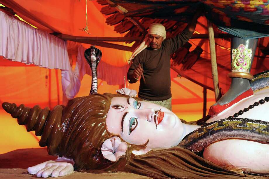 An Indian artist gives final touches to an idol of Hindu God Shiva at the Akhara Pandal during the Maha Kumbh festival in Allahabad on February 3, 2013.  The Kumbh Mela in the town of Allahabad will see up to 100 million worshippers gather over 55 days to take a ritual bath in the holy waters, believed to cleanse sins and bestow blessings. Photo: SANJAY KANOJIA, AFP/Getty Images / AFP