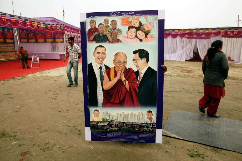 An Indian worker carries a portrait of Tibetan spiritual leader the Dalai Lama in preparation of his Sunday visit at Sangam, the confluence of rivers Ganges, Yamuna and mythical Saraswati, during Mahakumbh festival in Allahabad, india, Saturday, Feb. 2, 2013. Millions of Hindu pilgrims are expected to attend the Maha Kumbh festival, which is one of the world's largest religious gatherings that lasts 55 days and falls every 12 years. Photo: Rajesh Kumar Singh, Associated Press / AP