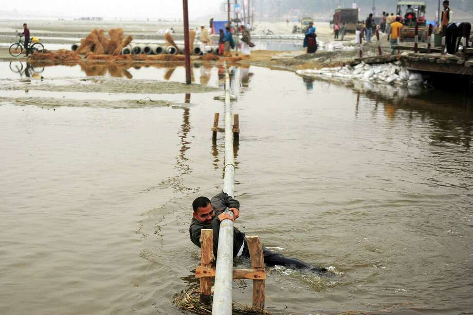 A pedestrian holds on after slipping off a pipe, which he used to cross a section of the River Ganges, following the closure of a nearby pontoon bridge during the Maha Kumbh festival, in Allahabad on February 2, 2013.  The Kumbh Mela in the town of Allahabad will see up to 100 million worshippers gather over 55 days to take a ritual bath in the holy waters, believed to cleanse sins and bestow blessings. Photo: SANJAY KANOJIA, AFP/Getty Images / AFP