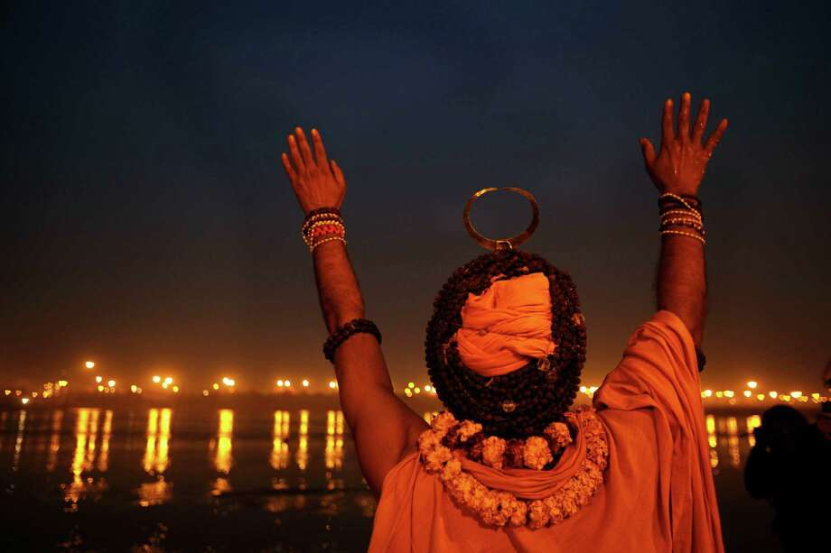 A Sadhu, or Hindu holy man, performs evening rituals at Sangam, the confluence of the rivers Ganges, Yamuna and mythical Saraswati during the Maha Kumbh Mela in Allahabad, India. Millions of Hindu pilgrims are expected to attend the Maha Kumbh festival, which is one of the world's largest religious gatherings that lasts 55 days and falls every 12 years. During the festival pilgrims bathe in the holy Ganges River in a ritual they believe can wash away their sins. Photo: Rajesh Kumar Singh, Associated Press / AP