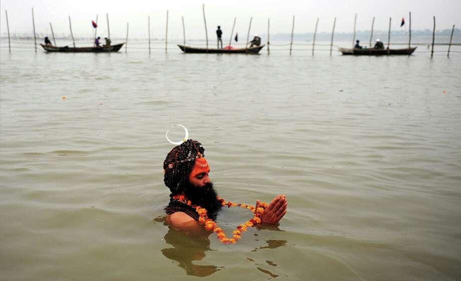 An Indian sadhu - holy man - takes a 'holy dip' at the 'Sangam', the confluence of the rivers Ganges, Yamuna and mythical Saraswati during the Maha Kumbh festival in Allahabad on January 31, 2013.  The Kumbh Mela in the town of Allahabad will see up to 100 million worshippers gather over 55 days to take a ritual bath in the holy waters, believed to cleanse sins and bestow blessings. Photo: SANJAY KANOJIA, AFP/Getty Images / AFP