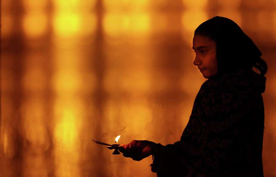 A Hindu devotee offers her evening prayers on the bank of the river Ganges during the Maha Kumbh fes