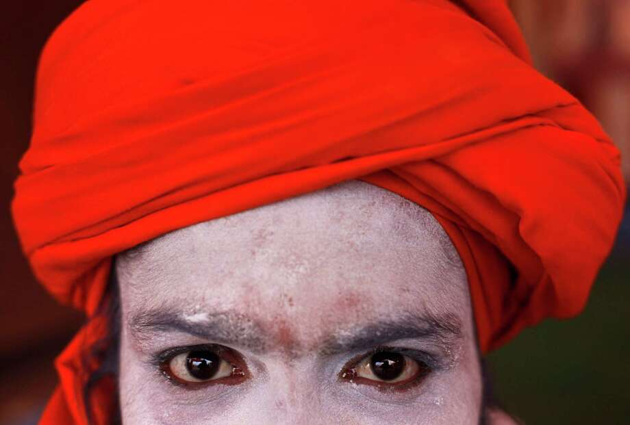 "A Hindu holy man poses for a photograph at Sangam, the confluence of the Ganges and Yamuna rivers on the occasion of ""Paush Purnima"", during the Maha Kumbh festival in Allahabad, India, Sunday, Jan. 27, 2013. Hundreds of thousands of Hindu pilgrims are expected to take a ritual dip at Sangam on Sunday. Photo: Rajesh Kumar Singh, Associated Press / AP"