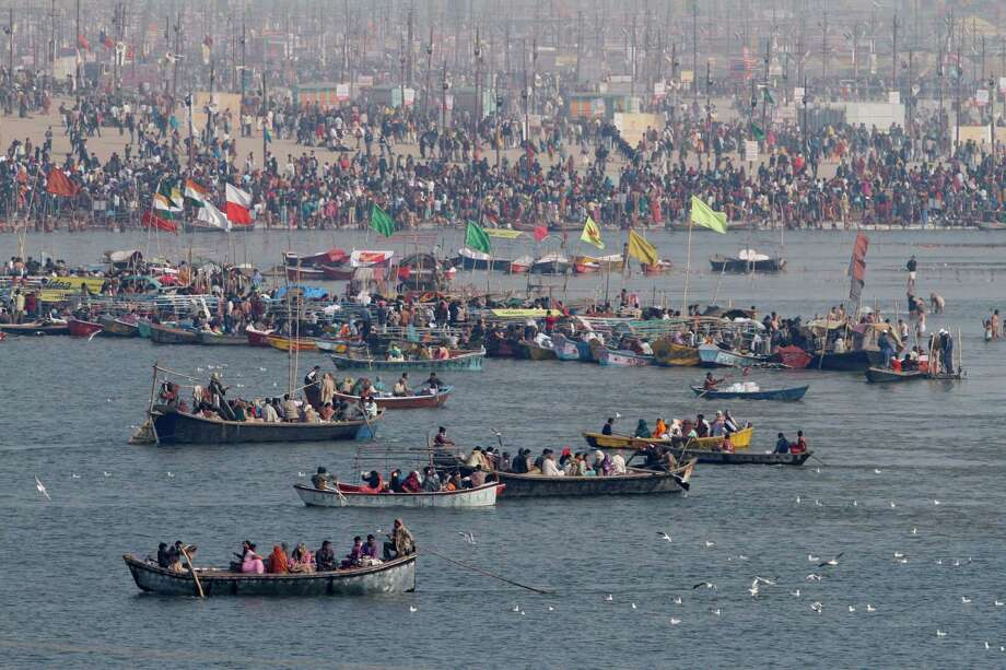 "Hindu devotees travel on boats at at ""Sangam,"" the meeting point of Indian holy rivers of Ganges and Yamuna on the occasion of ""Paush Purnima,"" auspicious according to Hindu calendars, during the Maha Kumbh festival in Allahabad, India, Sunday, Jan. 27, 2013. Hundreds of thousands of Hindu pilgrims are expected to take a ritual dip at Sangam on Sunday. Millions of Hindu pilgrims are likely to attend the Maha Kumbh festival, which is one of the world's largest religious gatherings that lasts 55 days and falls every 12 years. Photo: Rajesh Kumar Singh, Associated Press / AP"