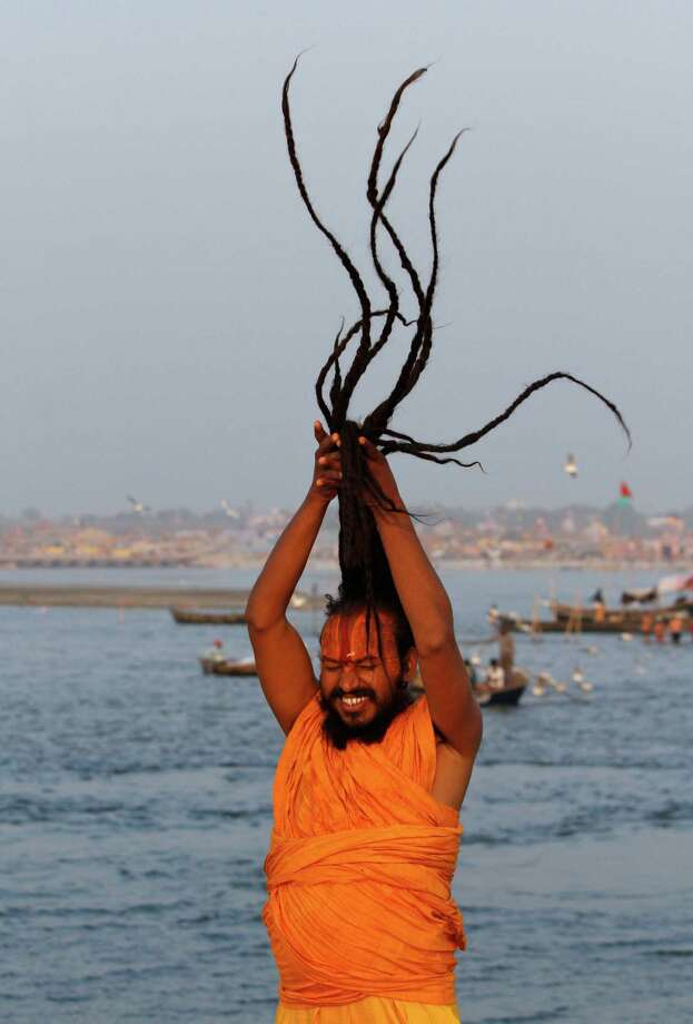 A Sadhu, or Hindu holy man, ties his hair at Sangam, the confluence of the holy rivers Ganges and Yamuna and mythical Saraswati at the Maha Kumbh Mela in Allahabad, India, Saturday, Jan. 19, 2013.  Millions of Hindu pilgrims are expected to attend the Maha Kumbh festival, which is one of the world's largest religious gatherings that lasts 55 days and falls every 12 years. During the festival pilgrims bathe in the holy Ganges River in a ritual they believe can wash away their sins. Photo: Rajesh Kumar Singh, Associated Press / AP
