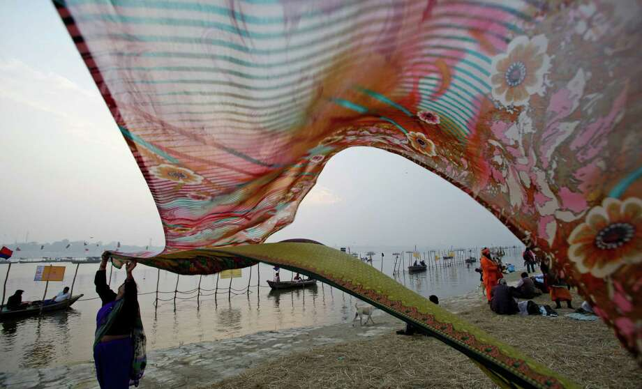 Hindu devotees dry their clothes after a holy dip at Sangam, the confluence of the Ganges, Yamuna and mythical Saraswati River, during the Maha Kumbh Mela, in Allahabad, India, Friday, Jan. 18, 2013. Millions of Hindu pilgrims are expected to attend the Maha Kumbh festival, which is one of the world's largest religious gatherings that lasts 55 days and falls every 12 years. During the festival pilgrims bathe in the holy Ganges River in a ritual they believe can wash away their sins. Photo: Rajesh Kumar Singh, Associated Press / AP