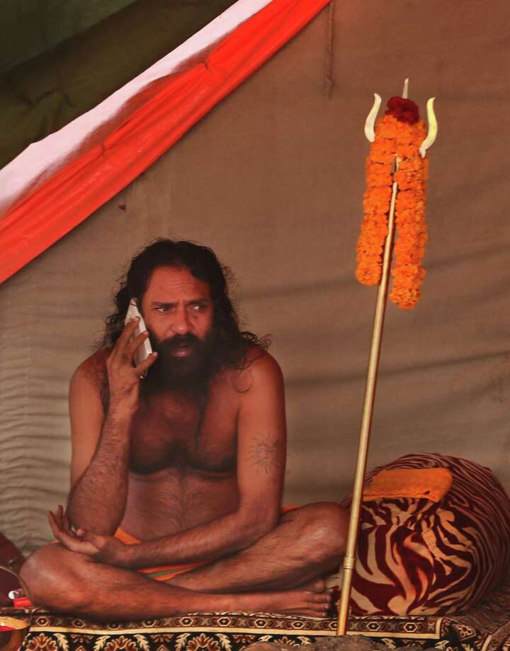 An Indian Hindu holy man talks on his mobile outside his camp at Sangam, the confluence of the Rivers Ganges, Yamuna and mythical Saraswati during the Maha Kumbh Mela, in Allahabad, India, Tuesday, Jan. 15, 2013. Millions of devout Hindus led by naked ascetics with ash smeared on their bodies plunged into the frigid waters of India's holy Ganges River on Monday in a ritual they believe can wash away their sins. The ceremony in the northern city of Allahabad took place on the most auspicious day of the Kumbh Mela, or Pitcher Festival, one of the world's largest religious gatherings that lasts 55 days. Photo: Manish Swarup, Associated Press / AP