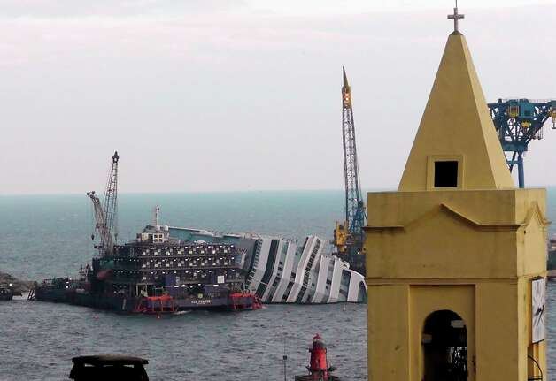 "FILE - This Jan. 11, 2013 file photo shows the cruise ship Costa Concordia leaning on its side, near the shore of the Tuscan island of Giglio, Italy.  Thirty-two people died when the ship ran aground on Jan. 13, 2012. Cruise watchers looking back at the industry's past year say the Concordia disaster affected everything from prices to safety drills to first-time cruisers, but bookings appear to be picking up as the 2013 cruise booking season gets under way. The first three months of each year are known as ""wave season,""a period when many cruisers book trips as they plan ahead for summer vacations.  (AP Photo/Paolo Santalucia, file) Photo: Paolo Santalucia"