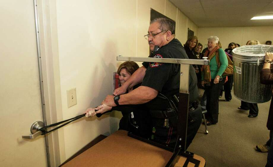 Tammy Harlan, of Humble ISD, and Klein ISD Police Chief Guadalupe Rocha secure a door with an ethernet cord as participants of the Intruderology training make a barricade during a hostile intruder simulation in the HISD Police Department headquarters. Photo: Nick De La Torre, Staff / © 2010 Houston Chronicle